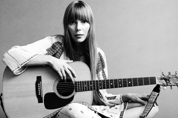 20th November 1968:  Portrait of American musician Joni Mitchell seated on the floor with her acoustic guitar in her lap.  This image was from a shoot for the fashion magazine Vogue.  Mitchell wears a white cotton dress.  (Photo by Jack Robinson/Hulton Archive/Getty Images)