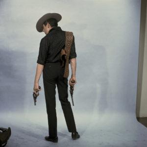 Serge Gainsbourg en tenue de cow-boy pour la séance photo de la pochette du titre 'Vilaine fille mauvais garçon' à Paris, France, en décembre 1962.